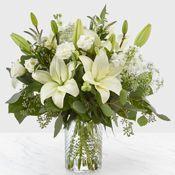 Florero con liliums blancos ,alstroemerias y mas alto aprox 35 cms x 35 cms