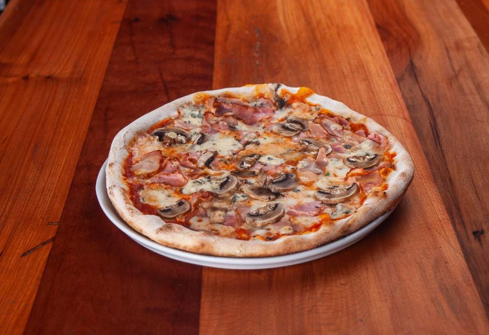 Pizza del pizzaiolo. salsa de tomates, mozzarella fior di latte, jamon acaramelado, champiñones, tocino y queso azul. Caja pizza 30cm.
