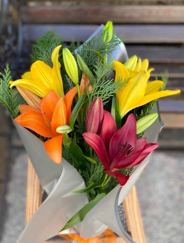 Ramo de lilium 3 varas con 3 flores por vara, envueltas en papel.